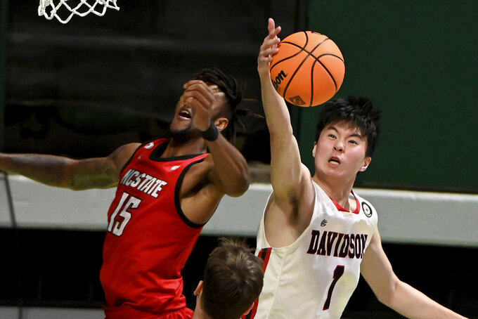 Davidson forward Hyunjung Lee (1) grabs a rebound in from of North Carolina State forward Manny Bates (15) in the second half of an NCAA college basketball game in the first round of the NIT, Thursday, March 18, 2021, in Denton, Texas. North Carolina State won 75-61. (AP Photo/Matt Strasen)