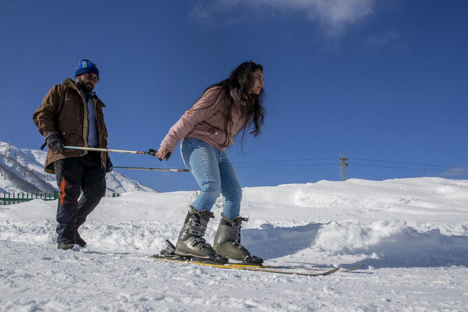 """Ramasha Rizwan, an Indian tourist is helped by a Kashmiri ski instructor to ski down a slop in Afarwat, Gulmarg, northwest of Srinagar, Indian controlled Kashmir, Sunday, Jan. 10, 2021. Rizwan, said Kashmir is beautiful, it is mesmerizing, and the views are spectacular. I snapped my friends, and they were like, oh are you abroad? How do you go there? I said no, it's Kashmir. And I am really enjoying myself right now""""(AP Photo/ Dar Yasin)"""
