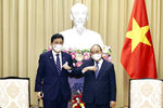 Vietnamese President Nguyen Xuan Phuc, right, and Japanese Defense Minister Nobuo Kishi stand for photo in Hanoi, Vietnam  Sunday, Sept. 12, 2021. Japan can now give defense equipment and technology to Vietnam under an agreement signed Saturday, as the two countries step up their military cooperation amid worries about China's growing military influence. (Hoang Thong Nhat/VNA via AP)