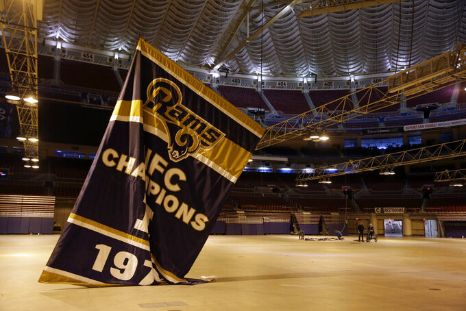 FILE - In this Jan. 14, 2016, file photo, championship banners are removed from the Edward Jones Dome, former home of the St. Louis Rams football team, in St. Louis. The Missouri Supreme Court has ruled that a lawsuit filed over the Rams' departure from St. Louis will be heard in a St. Louis courtroom, a defeat for the NFL team's owner who sought to send the case to arbitration. The court issued its ruling Tuesday, Sept. 3, 2019, in a lawsuit filed by St. Louis city and county and the St. Louis Regional Convention and Sports Complex Authority, which owns the domed stadium where the Rams formerly played.  (AP Photo/Jeff Roberson, File)