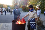 Jondavid Longo, mayor of Slippery Rock, Pa., center, presides over a Boy Scouts flag retirement ceremony where worn out flags are cut up and burned on Tuesday, Oct. 13, 2020 in Slippery Rock. Longo has opened a campaign office and is recruiting young people to register and vote for President Donald Trump. (AP Photo/Ted Shaffrey)