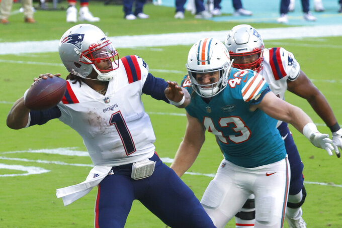 New England Patriots quarterback Cam Newton (1) aims a pass as Miami Dolphins outside linebacker Andrew Van Ginkel (43) attempts to defend, during the second half of an NFL football game against the Miami Dolphins, Sunday, Dec. 20, 2020, in Miami Gardens, Fla. (AP Photo/Joel Auerbach)
