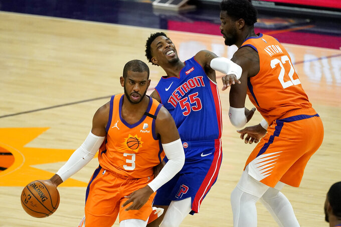 Phoenix Suns guard Chris Paul (3) drives as Detroit Pistons guard Delon Wright (55) is blocked by center Deandre Ayton (22) during the second half of an NBA basketball game, Friday, Feb. 5, 2021, in Phoenix. (AP Photo/Matt York)