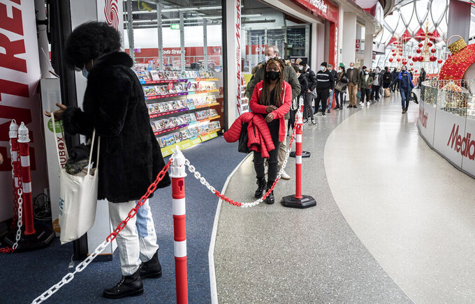 People wearing face masks to prevent the spread of the coronavirus wait in a line to enter a shop in Liege, Belgium, Tuesday, Dec. 1, 2020. Non-essential shops in Belgium are reopening on Tuesday in the wake of encouraging figures about declining infection rates and hospital admissions because of the coronavirus. (AP Photo/Valentin Bianchi)