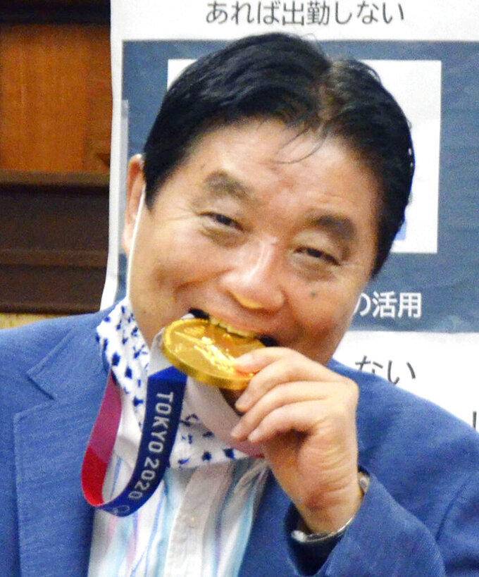 Nagoya Mayor Takashi Kawamura bites the Olympic gold medal of Miu Goto, a member of Japan softball team who won the event at the 2020 Summer Olympics, at the city office building in Nagoya, central Japan, Wednesday, Aug. 4, 2021. (Kyodo News via AP)