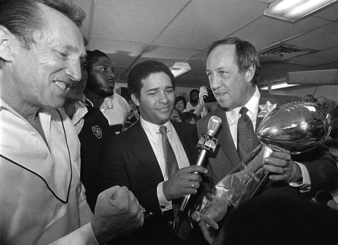 FILE - In this Jan. 25, 1981, file photo, NFL Commissioner Pete Rozelle, right, presents the Super Bowl XV trophy to Oakland Raiders managing general partner Al Davis, left, pumping his fist, after Sunday's Super Bowl game against the Philadelphia Eagles in New Orleans. Sportscaster Bryant Gumble holds the microphone at center. (AP Photo/File)