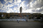 Children play soccer on a paved soccer field, where Argentina's soccer star Carlos Tevez played according to residents, during a lockdown to curb the spread of COVID-19 in the Fuerte Apache neighborhood of  Buenos Aires, Argentina, Monday, June 15, 2020. Argentina is far from the worst-hit country in Latin America by the new coronavirus, but the impact on the youngest players of canceling soccer shows the subtle long-term damage being wrought by the pandemia. (AP Photo/Natacha Pisarenko)