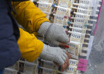 A Christmas lottery seller puts some tickets on display in Madrid, Spain, Saturday, Dec. 21, 2019. Spain's bumper Christmas lottery draw known as El Gordo, or The Fat One will be held on Dec. 22. (AP Photo/Paul White)