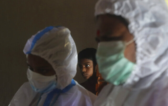 A boy looks on as health workers screen people for COVID-19 symptoms at a residential building in Dharavi, one of Asia's biggest slums, in Mumbai, India, Friday, Aug. 7, 2020. As India hit another grim milestone in the coronavirus pandemic on Friday, crossing 2 million cases and more than 41,000 deaths, community health volunteers went on strike complaining they were ill-equipped to respond to the wave of infection in rural areas. (AP Photo/Rafiq Maqbool)