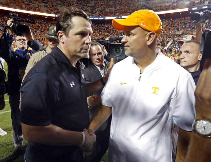 Tennessee head coach Jeremy Pruitt shakes hands with South Carolina head coach Will Muschamp after an NCAA college football game Saturday, Oct. 26, 2019, in Knoxville, Tenn. Tennessee won 41-21. (AP Photo/Wade Payne)