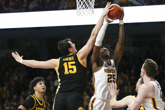 Iowa's Ryan Kriener (15) blocks the shot of Minnesota's Daniel Oturu (25) during an NCAA college basketball game Sunday, Feb. 16, 2020, in Minneapolis. (AP Photo/Stacy Bengs)