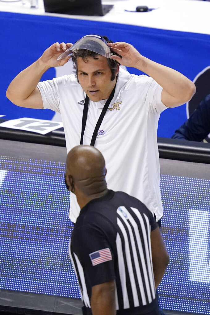 Georgia Tech head coach Josh Pastner adjusts his face shield as he talks to a ref during the second half of an NCAA college basketball game against Miami in the quarterfinal round of the Atlantic Coast Conference tournament in Greensboro, N.C., Thursday, March 11, 2021. (AP Photo/Gerry Broome)