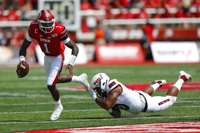 Utah quarterback Tyler Huntley (1) breaks from a Northern Illinois tackler in the first half of an NCAA college football game Saturday, Sept. 9, 2019, Salt Lake City. (AP Photo/Rick Bowmer)