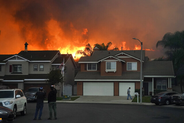 FILE - In this Oct. 27, 2020 file photo, residents watch as the Blue Ridge Fire burns above blacked-out homes in Chino Hills, Calif. Southern California utilities say they may cut power to more than 300,000 customers this week as dry, gusty weather raises the threat of wildfire danger. The National Weather Service is issuing red flag warnings of extreme fire danger over much of the region because of dry vegetation, low humidity and gusty Santa Ana winds.  (AP Photo/Jae C. Hong, File)