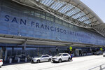 FILE - In this July 11, 2017, file photo, vehicles wait outside the international terminal at San Francisco International Airport in San Francisco. Video captured the moment that an off-course Air Canada jet flew just a few dozen feet over the tops of four other jetliners filled with passengers. On Tuesday, Sept. 25, 2018, the National Transportation Safety Board will consider the probable cause of the close call at the airport. (AP Photo/Marcio Jose Sanchez, File)