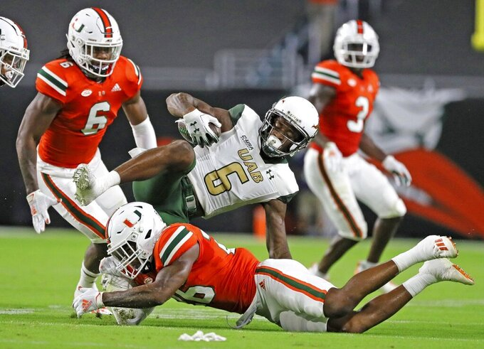 Miami safety Gurvan Hall Jr., bottom, dives for UAB's Austin Watkins JR. (6) during an NCAA college football game in Miami Gardens, Fla., Thursday, Sept. 10, 2020. (Al Diaz/Miami Herald via AP)