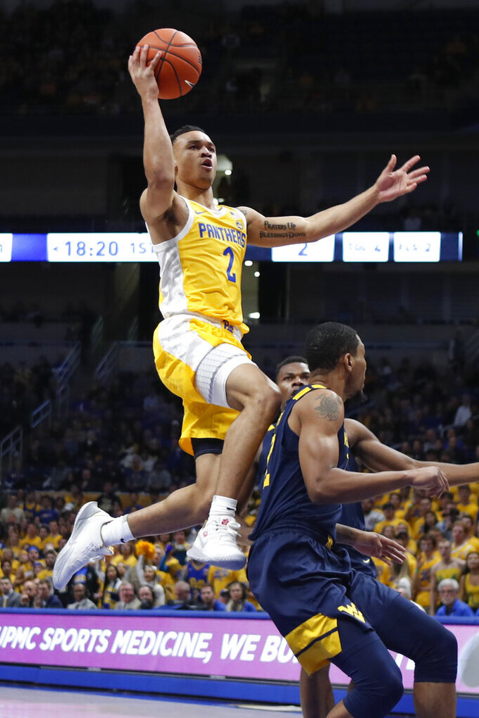 Pittsburgh's Trey McGowens (2) goes up to shoot over West Virginia's Taz Sherman, right, during the first half of an NCAA college basketball game, Friday, Nov. 15, 2019, in Pittsburgh. (AP Photo/Keith Srakocic)