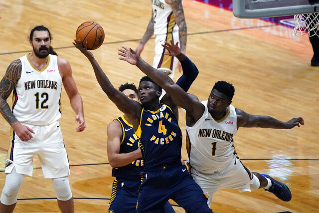 Indiana Pacers guard Victor Oladipo (4) and New Orleans Pelicans forward Zion Williamson (1) battle under the basket in the second half of an NBA basketball game in New Orleans, Monday, Jan. 4, 2021. (AP Photo/Gerald Herbert)