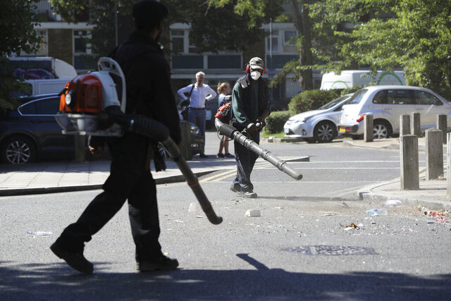 Volunteers clean up the streets following overnight violent confrontations with police, in the Brixton area of London, Thursday June 25, 2020.  Authorities have reported some fifteen officers were injured and four people were arrested following the incident.  (Jonathan Brady/PA via AP)