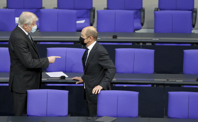 German Interior Minister Horst Seehofer, left, and German Finance Minister Olaf Scholz, right, talk as they arrive for a meeting of the German federal parliament, Bundestag, at the Reichstag building in Berlin, Germany, Wednesday, Jan. 13, 2021. One topic of the meeting are the current developments of the new coronavirus pandemic in Germany. (AP Photo/Michael Sohn)