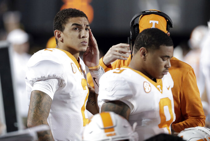 Tennessee quarterback Jarrett Guarantano, left, looks at the scoreboard late in the fourth quarter of an NCAA college football game against Vanderbilt, Saturday, Nov. 24, 2018, in Nashville, Tenn. (AP Photo/Mark Humphrey)