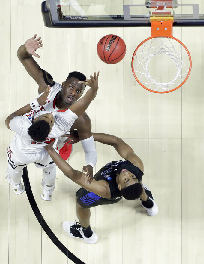 Texas Tech's Jarrett Culver heads to the basket teammate Norense Odiase, top, and Buffalo's CJ Massinburg, bottom, watch during the second half of a second round men's college basketball game in the NCAA Tournament Sunday, March 24, 2019, in Tulsa, Okla. Texas Tech won 78-58. (AP Photo/Jeff Roberson)