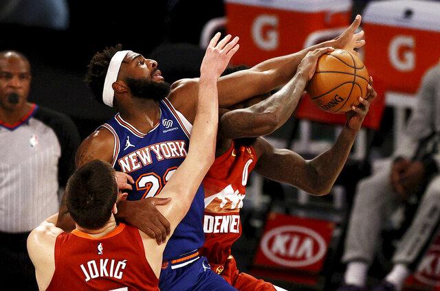 New York Knicks' Mitchell Robinson (23) defends against Denver Nuggets' Nikola Jokic as Nuggets' JaMychal Green (0) grabs a rebound during an NBA basketball game Sunday, Jan. 10, 2021, in New York. (Elsa/Pool Photo via AP)