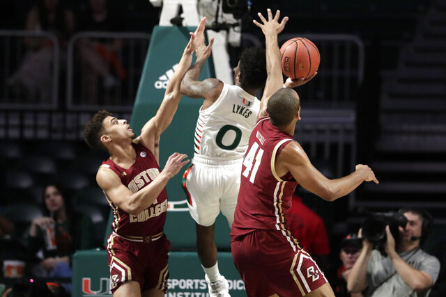 Miami guard Chris Lykes (0) is fouled by Boston College guard Derryck Thornton, left, as forward Steffon Mitchell (41) defends during the first half of an NCAA college basketball game, Wednesday, Feb. 12, 2020, in Coral Gables, Fla. (AP Photo/Lynne Sladky)