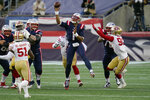 New England Patriots quarterback Cam Newton, center, passes under pressure from San Francisco 49ers linebacker Azeez Al-Shaair (51) and defensive end Dion Jordan, right, in the first half of an NFL football game, Sunday, Oct. 25, 2020, in Foxborough, Mass. (AP Photo/Charles Krupa)