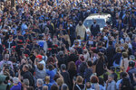 """People gather to pay their last respect to the late Greek composer Mikis Theodorakis, as the hearse drives among the crowd, prior to his burial, in Chania, Crete island, Greece, Thursday, Sept. 9 2021. Theodorakis died Thursday, Sept. 2, 2021 at 96. He penned a wide range of work, from somber symphonies to popular TV and film scores, including for """"Serpico"""" and """"Zorba the Greek."""" He is also remembered for his opposition to the military junta that ruled Greece from 1967-1974, when he was persecuted and jailed and his music outlawed. (AP Photo/Harry Nakos)"""