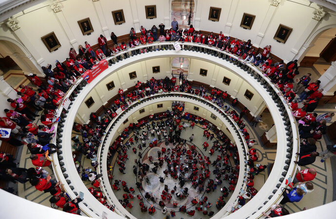 In this March 11, 2019, photo, Educators attending a rally to support funding for public schools in Texas fill the rotunda of the state Capitol in Austin, Texas. Cost-cutting states are trying to keep schools happy as teacher unrest over low pay and overcrowded classrooms continues. But pressure from voters is forcing states to put more money on the table as much as much as picket lines. (AP Photo/Eric Gay)