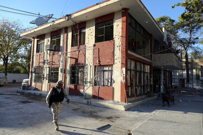 A soldier walks past City Hall that is riddled with bullet holes, in Villa Union, Mexico, Monday, Dec. 2, 2019. The small town near the U.S.-Mexico border began cleaning up Monday even as fear persisted after 22 people were killed in a weekend gun battle between a heavily armed drug cartel assault group and security forces. (AP Photo/Eduardo Verdugo)