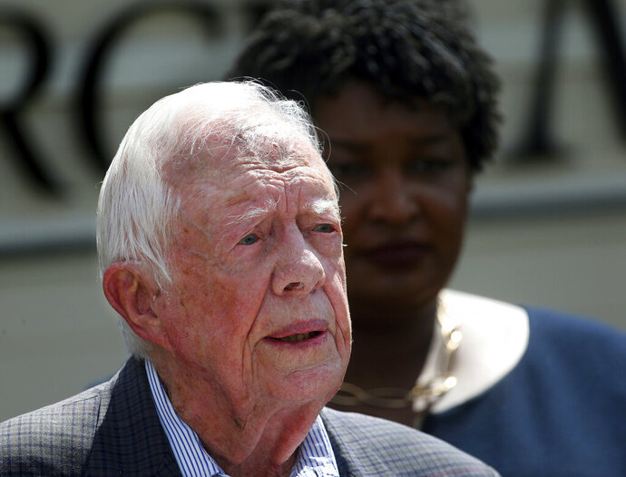 FILE- In this Sept. 18, 2018 file photo, former President Jimmy Carter speaks as Democratic gubernatorial candidate Stacey Abrams listens during a news conference to announce her rural health care plan, in Plains, Ga. Carter is now the longest-living president in American history. The 39th president on Friday, March 15, 2019, reached the age of 94 years, 172 days - one day beyond the lifespan of George H.W. Bush, who died in November. (AP Photo/John Bazemore, File)