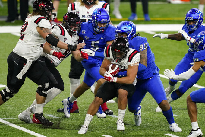 Ball State running back Tye Evans is stopped by Buffalo defensive tackle Tyrece Woods Jr. (95) during the first half of the Mid-American Conference championship NCAA college football game, Friday, Dec. 18, 2020, in Detroit. (AP Photo/Carlos Osorio)