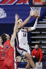 Gonzaga forward Corey Kispert, right, shoots in front of Dixie State forward Jacob Nicolds during the first half of an NCAA college basketball game in Spokane, Wash., Tuesday, Dec. 29, 2020. (AP Photo/Young Kwak)