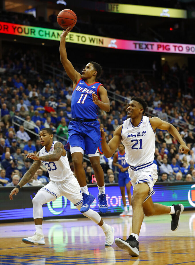 DePaul's Charlie Moore (11) goes to the basket against Seton Hall's Shavar Reynolds (33) and Ike Obiagu (21) during the first half of an NCAA college basketball game Wednesday, Jan. 29, 2020 in Newark, N.J. (AP Photo/Noah K. Murray)