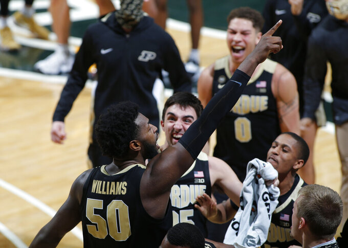 Purdue's Trevion Williams, left, celebrates with teammates following an NCAA college basketball game against Michigan State, Friday, Jan. 8, 2021, in East Lansing, Mich. Purdue won 55-54. (AP Photo/Al Goldis)