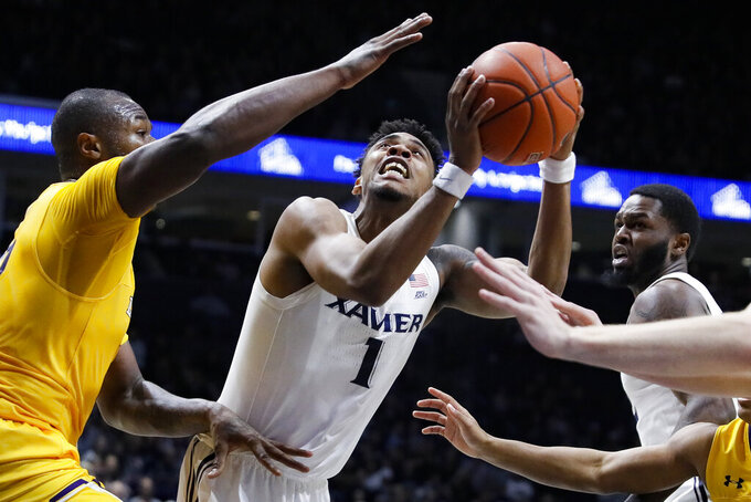Xavier's Paul Scruggs (1) shoots against Lipscomb's Ahsan Asadullah, left, during the first half of an NCAA college basketball game, Saturday, Nov. 30, 2019, in Cincinnati. (AP Photo/John Minchillo)