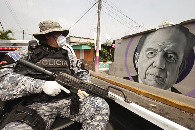 A National Civil Police Special Forces officer patrols past a mural of Armando Bukele, father of El Salvador's President Nayib Bukele, which was painted by supporters of the president outside a cultural center as a thank you gesture for creating the center when he was mayor, during the enforcement of the coronavirus-related quarantine, in the Iberia area of San Salvador, El Salvador, Thursday, April 23, 2020. When the coronavirus appeared, President Bukele closed the borders and airports and imposed a mandatory home quarantine for all except those working in the government, hospitals, pharmacies or other designated businesses. People were allowed out only to buy groceries, and violators were detained, with more than 2,000 being held for 30-day stints. (AP Photo/Salvador Melendez)