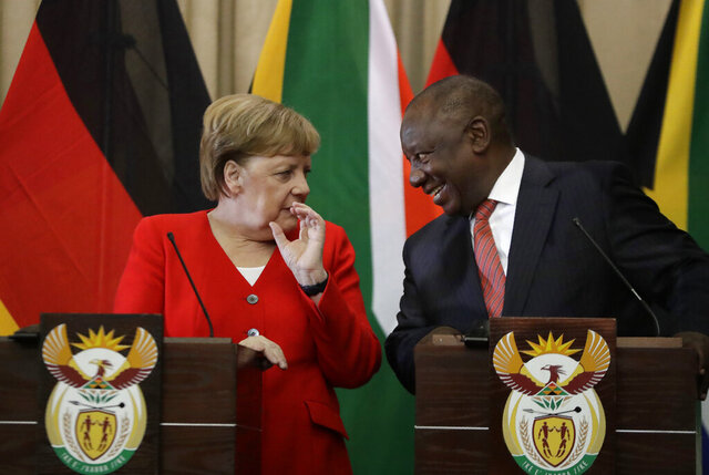 German Chancellor Angela Merkel, left, and South African President Cyril Ramaphosa react, during a press conference at the government's Union Buildings in Pretoria, South Africa, Thursday, Feb. 6, 2020. Merkel is in South Africa to discuss trade, investment and energy issues with Berlin's largest trading partner in Africa. (AP Photo/Themba Hadebe)