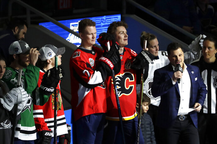 Ottawa Senators' Brady Tkachuk, left, and his brother Calgary Flames' Matthew Tkachuk watch the Skills Competition, part of the NHL All-Star weekend, Friday, Jan. 24, 2020, in St. Louis. (AP Photo/Jeff Roberson)