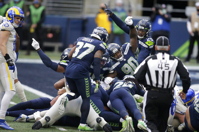CORRECTS INFORMATION ABOUT THE PLAY - Seattle Seahawks players, including defensive tackle Jarran Reed (90) react after stopping Los Angeles Rams quarterback Jared Goff near the goal line during the second half of an NFL football game, Sunday, Dec. 27, 2020, in Seattle. (AP Photo/Scott Eklund)