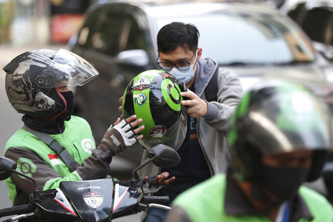 A Gojek driver, left, gives a helmet to a customer in Jakarta, Indonesia, Monday, May 17, 2021. Indonesian ride hailing company Gojek and e-commerce firm Tokopedia said Monday that they are merging, in the largest ever deal in the country's history. (AP Photo/Achmad Ibrahim)