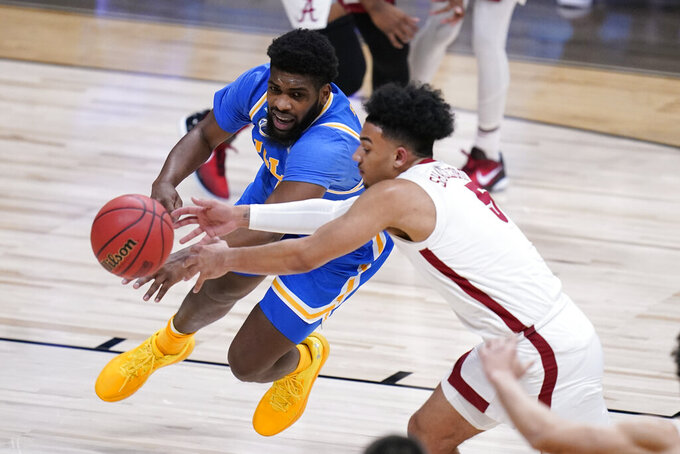 UCLA forward Cody Riley (2) and Alabama guard Jaden Shackelford (5) chase a loose ball in the first half of a Sweet 16 game in the NCAA men's college basketball tournament at Hinkle Fieldhouse in Indianapolis, Sunday, March 28, 2021. (AP Photo/Michael Conroy)