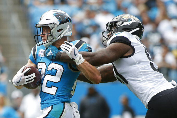 Jacksonville Jaguars defensive end Yannick Ngakoue (91) reaches for Carolina Panthers running back Christian McCaffrey (22) during the first half of an NFL football game in Charlotte, N.C., Sunday, Oct. 6, 2019. (AP Photo/Brian Blanco)