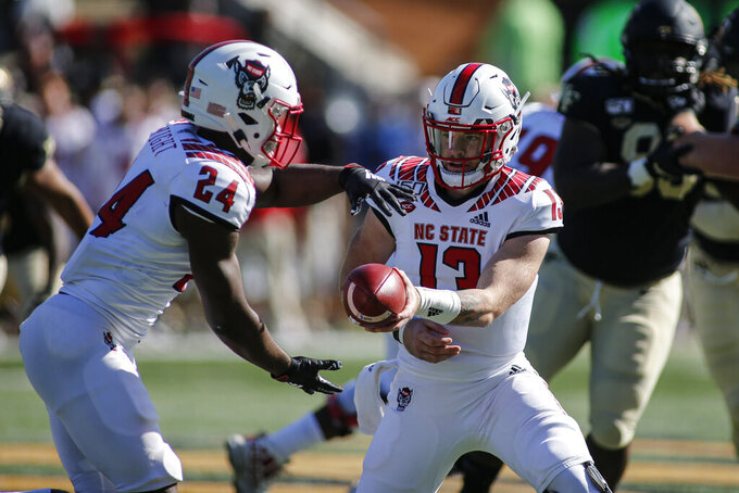 North Carolina State quarterback Devin Leary, right, hands off to running back Zonovan Knight in the first half against Wake Forest in an NCAA college football game in Winston-Salem, N.C., Saturday, Nov. 2, 2019. Wake Forest won 44-10. (AP Photo/Nell Redmond)