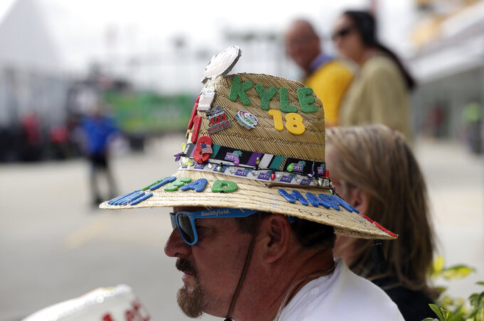 Racing fan Richard Boyer, of Sebastian, Fla., wears a hat decorated for the NASCAR Cup Series auto race at the Homestead-Miami Speedway, Saturday, Nov. 17, 2018, in Homestead, Fla. (AP Photo/Lynne Sladky)