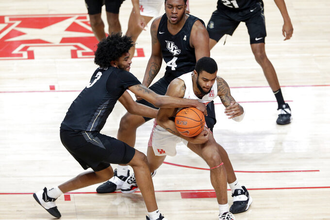 Central Florida forward Isaiah Adams (3) fouls on the attempted steal from Houston forward Reggie Chaney (32) during the first half of an NCAA college basketball game Sunday, Jan. 17, 2021, in Houston. (AP Photo/Michael Wyke)