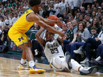 Michigan State's Xavier Tillman, right, and Michigan's David DeJulius battle for the ball during the second half of an NCAA college basketball game, Sunday, Jan. 5, 2020, in East Lansing, Mich. (AP Photo/Al Goldis)