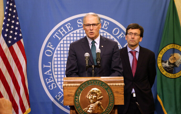 Gov. Jay Inslee, left, addresses a news conference with Attorney General Bob Ferguson following an earlier announcement that Washington's Supreme Court unanimously struck down the state's death penalty, Thursday, Oct. 11, 2018, in Olympia, Wash. Washington has had a moratorium on executions since 2014, but the ruling makes it the 20th state to do away with capital punishment by legislative act or court decree. The court converted the sentences of the eight people on Washington's death row to life in prison. (AP Photo/Rachel La Corte)
